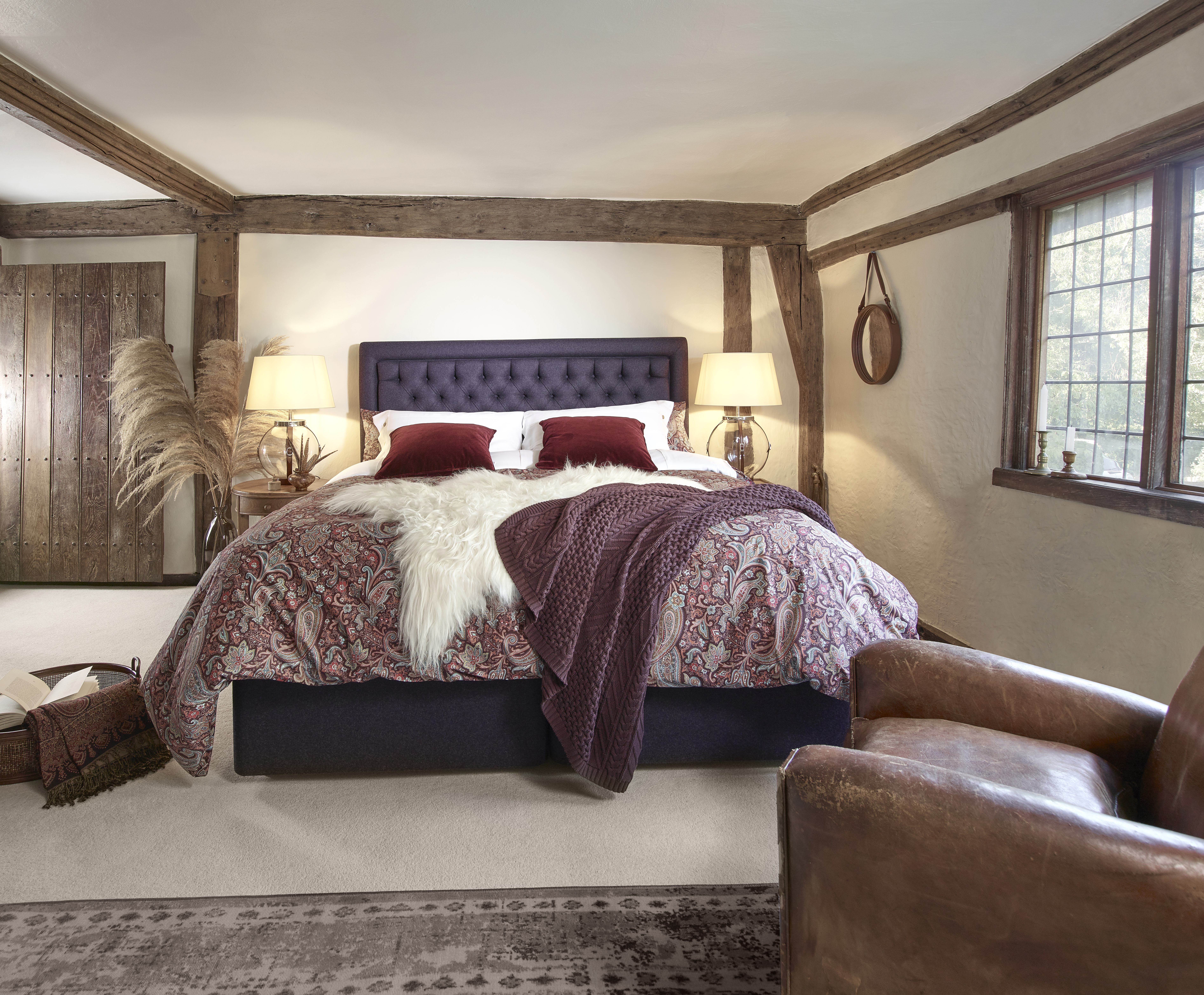 Beautiful Image of Adam Henson Camden bed range. Blue wool fabric headboard with deep red cushions and faux fur throw. Featured in a country style interior