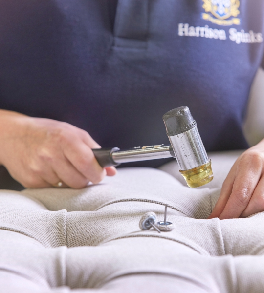 Artisan bedmakers at Harrison Spinks hammering buttons into a bespoke headboard